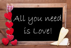 Chalkbord, Red And Yellow Hearts, All You Need Is Love. Chalkboard With English Quote All You Need Is Love. Red Textile And Wooden Yellow Hearts. Wooden Royalty Free Stock Photo
