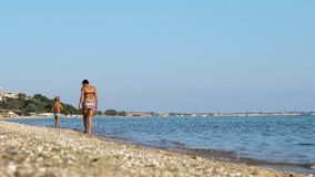 Mother and little son take a walk on beach coast. Chalkidiki, Greece - ?? September, 2017: Mother and little son take a walk on beach coast royalty free stock photos
