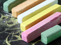Chalks with scribbles on chalkboard. Royalty Free Stock Photo