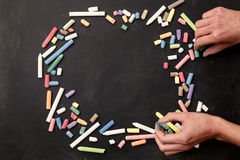 Chalks in a variety of colors arranged on a black background with hands Royalty Free Stock Image