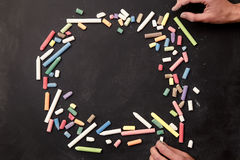 Chalks in a variety of colors arranged on a black background with hands Royalty Free Stock Photography