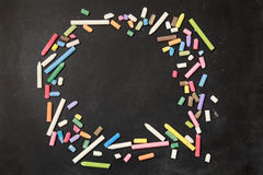 Chalks in a variety of colors arranged on a black background with hands Royalty Free Stock Photos