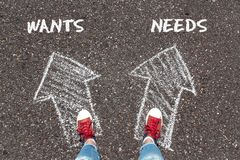 Chalky arrows Wants and Needs with feet in red sneakers from above standing on asphalt. Dilemma concept stock photography