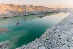 Mountain lake with emerald water at sunset. Chalky quarries - emerald blue water, vanilla sunset, white stones, pink sunset stock images