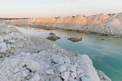 Mountain lake with emerald water at sunset. Chalky quarries - emerald blue water, vanilla sunset, white stones, pink sunset royalty free stock photography