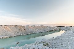 Mountain lake with emerald water at sunset. Chalky quarries - emerald blue water, vanilla sunset, white stones, pink sunset stock image
