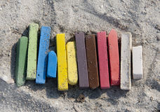 Chalky rainbow. Pastel colored chalk sticks on a sand Royalty Free Stock Image