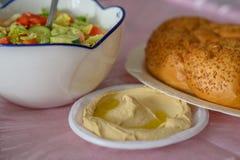 Challah chleb na stole dla Shabbat posiłku i tradycyjny domowej roboty hummus, sałatka na menchia stole ?ydowska kuchnia zdjęcie stock