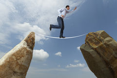 Challenge concept. Man walking on wire. Man walking on wire between two boulders. Challenge concept: difficult Stock Image