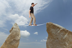 Challenge concept. Man walking on wire Royalty Free Stock Photography