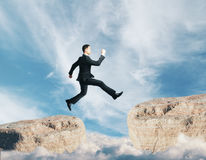 Challenge concept. Side view of young businessman jumping from cliff on sky background. Challenge concept Stock Images