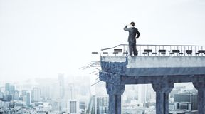Challenge and research concept. Businessman standing on broken bridge and looking into the distance on city backgroud with copy space. Challenge and research Royalty Free Stock Image
