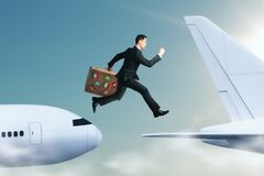 Challenge and success concept. Side view of young businessman with luggage jumping from plane to plane. Challenge and success concept stock photos