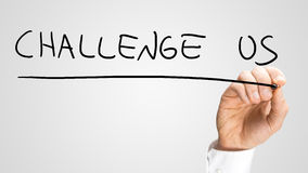 Challenge us. Male hand writing Challenge us on virtual screen Stock Image