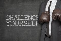 Challenge yourself on blackboard with businessman Stock Photography