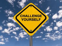Challenge yourself. Text 'challenge yourself' written on a yellow highway style sign in black uppercase letters, with a background of blue sky and small clouds Stock Photos