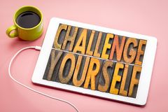 Challenge yourself - word abstract in wood type. Challenge yourself - word abstract in vintage letterpress printing blocks on a digital tbalet with a cup of stock images