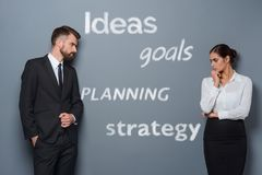 Challenges for business beginners. `Ideals`, `Goals`, `Planning`, `Strategy` letterings depicted on a gray wall. There are also two businessmen in the front of stock images