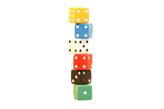 Challenging balancing act. 6 different coloured dice lying upon another isolated on white background royalty free stock image