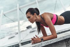 Challenging herself. Modern young woman in sports clothing keeping plank position while exercising outdoors stock image