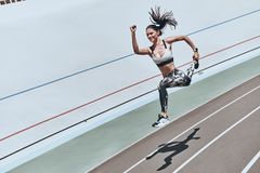 Challenging herself. Top view of young woman in sports clothing jumping and smiling while exercising outdoors royalty free stock photography