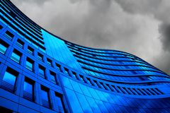 Challenging Times ahead. Gloomy Outlook for businesses. Blue office building with thunder clouds Royalty Free Stock Photos