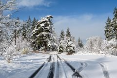 Challenging travel in a beautiful snow covered parking lot, snow covered trees. Blue ski, and white clouds royalty free stock images