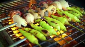 Chalota do alho e repreensão fresca das pimentas de pimentão sobre uma grade do fogo do carvão vegetal filme