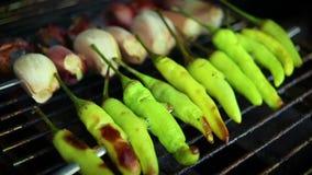 Chalota do alho e repreensão fresca das pimentas de pimentão sobre uma grade do fogo do carvão vegetal video estoque
