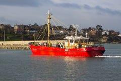 Chalutier se déplaçant à sa couchette dans un port en Irlande prenant l'abri pendant une tempête en mer d'Irlande image libre de droits