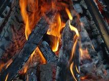 Chama alaranjada do fogo e close up queimado preto da lenha fotografia de stock