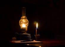 A chama do amarelo da lâmpada de querosene e uma vela iluminam o caderno com pena Imagem de Stock Royalty Free