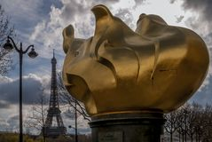 A chama famosa da liberdade com a torre Eiffel no fundo e em um céu dramático, Paris, França imagens de stock