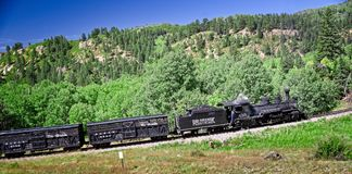 Rocky Mountain Train Adventure. Chama NM, USA, Sept. 19, 2017: A vintage steam locomoitve from the Cumbres & Toltec railroad climbs toward Chama Pass in early Stock Photography