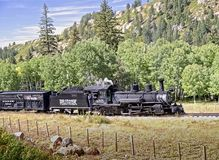 Rocky Mountain Train Adventure. Chama NM, USA, Sept. 19, 2017: A vintage steam locomoitve from the Cumbres & Toltec railroad climbs toward Chama Pass in early Royalty Free Stock Photos