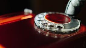Chamada anônima - uma mão gloved disca um número em um telefone retro velho no vermelho video estoque