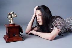 Chamada de espera triste atrativa da jovem mulher Foto de Stock