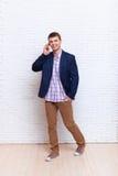 A chamada de telefone celular do homem de negócio fala Smartphone, homem de negócios Standing Over Wall Fotografia de Stock Royalty Free