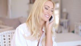 Chamada fêmea loura feliz no telefone que olha à esquerda video estoque