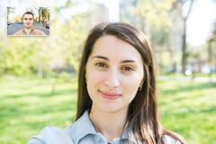 Chamada video da moça bonita com homem novo Imagem de Stock Royalty Free