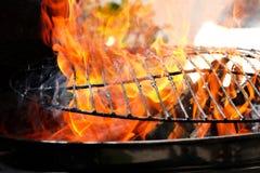 Chamas alaranjadas quentes que queimam uma grade de aço imagem de stock