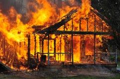 Chamas de queimadura da casa da vista lateral que saem de todas as aberturas fotografia de stock royalty free