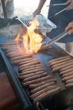Chamas que alargam-se acima na placa quente com salsichas e cebolas imagem de stock