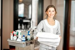 Chambermaid in the hotel corridor. Portrait of a young woman chambermaid holding a towel standing with maid cart full of cleaning stuff in the hotel corridor royalty free stock photo