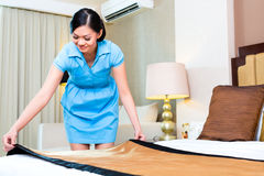 Chambermaid making bed in Asian hotel. Room Royalty Free Stock Photography