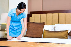 Chambermaid making bed in hotel room Stock Photo