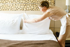 Chambermaid making a bed in a hotel room. Stock Photography
