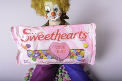 Sweethearts conversation candy hearts. Chambersburg Pa. USA 1/29/2019 antique clown doll with red hair and blue glass eyes holding bag of sweethearts stock photography