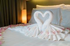 Chambre à coucher avec des cygnes de couples de la serviette sur le lit blanc Photos stock