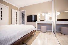 Chambre à coucher avec la TV et la coiffeuse photographie stock